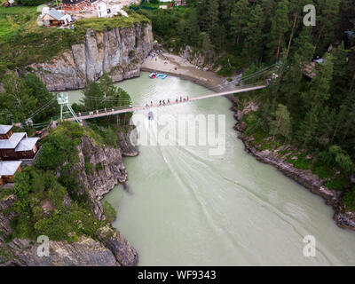 A small suspension bridge with columns on the rocky mountains along which people go when traveling to places of interest on the island of Patmos, Chem - Stock Photo