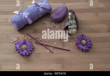 Spa concept.lavander oil flowers,candles, aromatic salt,soap and bath purple towels on wooden background - Stock Photo