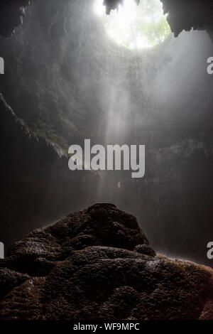 Light rays hitting limestone inside a dark deep cave called Jomblang cave which is 60m deep an iconic adventure spot in Indonesia - Stock Photo