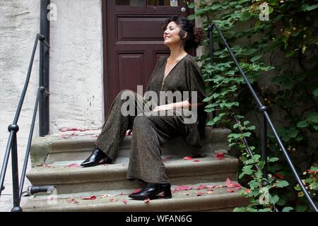 Mature Woman Sitting On Steps Outside House - Stock Photo