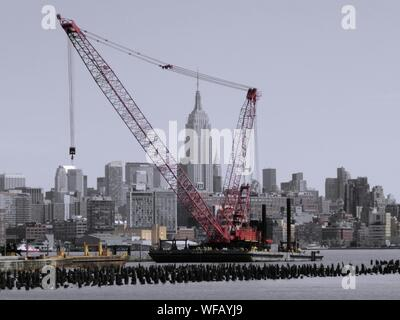 Empire State Building Seen Through Crane At Commercial Dock - Stock Photo
