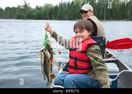 Portrait Of Happy Boy With Father Holding Dead Fish In Boat On Lake - Stock Photo