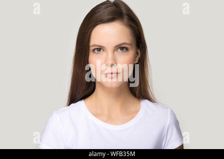 Headshot portrait of millennial young woman isolated in studio - Stock Photo