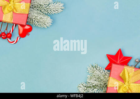 Christmas composition border with red gifts, holly berries and green fir branch on blue background - Stock Photo