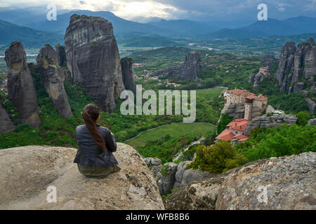 Rear View Of Woman Sitting On Rock - Stock Photo