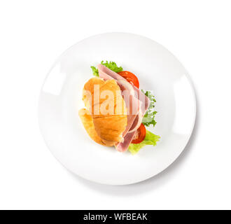 Big croissant with green salad and pork meat on isolate white background. Tasty croissant with a fork and dark place beside the plate Food photo. Heal - Stock Photo