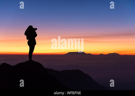 Silhouette Woman Photographing At Sunset - Stock Photo