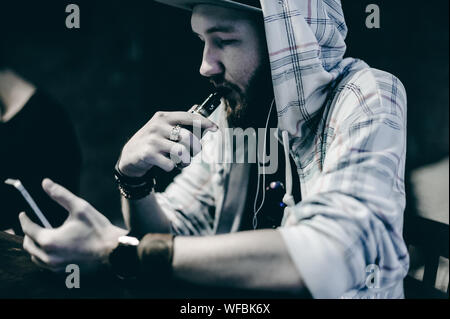 Young Man Smoking Electronic Cigarette While Using Phone At Table