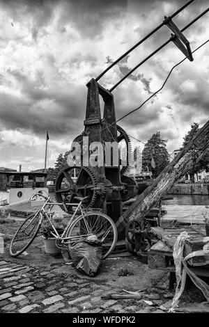 Bicycle Parked By Old Rusty Machinery Against Cloudy Sky - Stock Photo