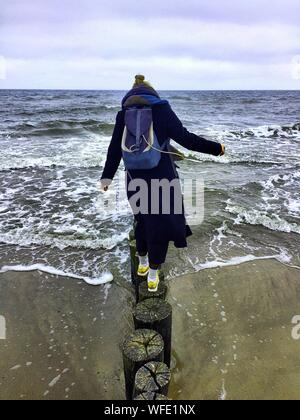 Rear View Of Female Hiker Walking On Wooden Post At Beach Against Sky - Stock Photo