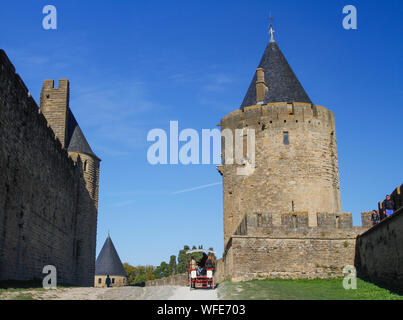 Tourists in horse drawn carriage, Carcassonne, France, Europe. Between fortified city double walls ramparts and watchtowers. French travel blue sky - Stock Photo