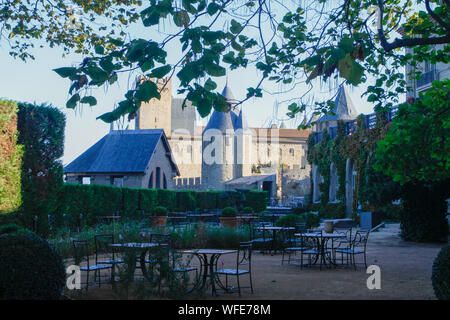 View from outdoor restaurant to La Cité, Carcassonne medieval city, watchtowers and stone walls. Blue sky, green leaves and trees. France, Europe - Stock Photo