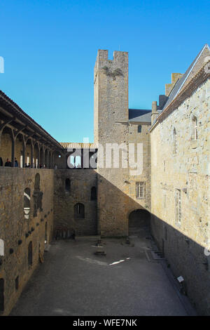 Tourists sightseeing in Carcassonne on sunny day, walk through covered archway with open courtyard below. France travel, Europe, Unesco site - Stock Photo