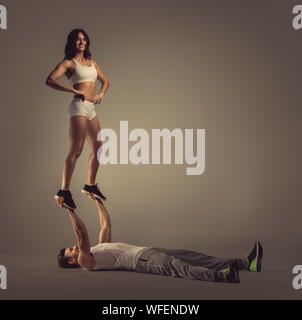 Young Athletic Couple Practicing Acroyoga Against Gray Background - Stock Photo