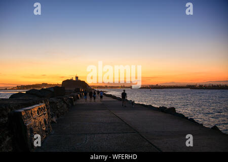 Nobbys Head Break Wall with Lighthouse and Harbour Entrance with Sunset Newcastle New South Wales NSW, Australia - Stock Photo