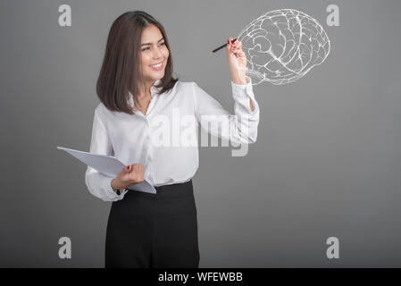 Digital Composite Image Of Young Woman Drawing Human Brain Standing Against Gray Background - Stock Photo