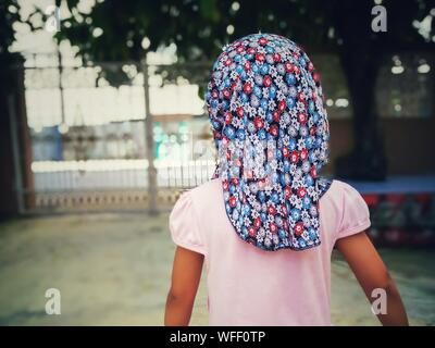 Rear View Of Girl Wearing Floral Headscarf - Stock Photo