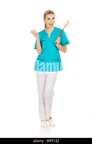 Portrait Of Smiling Nurse Wearing Scrubs While Holding Dental Equipment Against White Background - Stock Photo