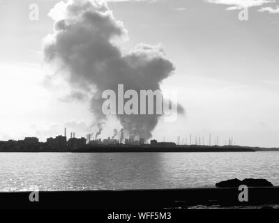 Smoke Emitting Through Chimney At Factory By Sea Against Sky - Stock Photo