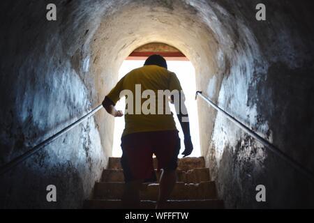 Man Walking Upstairs Toward Exit Of Subway - Stock Photo