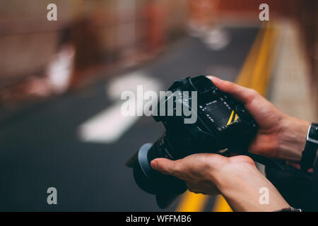 Cropped Image Of Hands Holding Digital Camera - Stock Photo