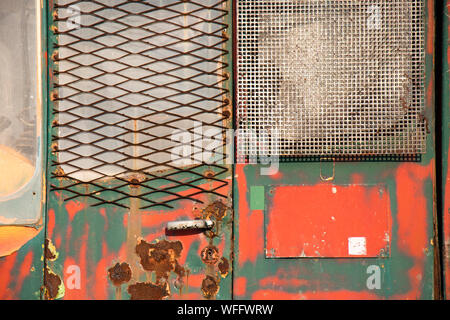 Weathered vibrant  layered green and red cracked paint on rusty  metal door, a detail of an old vintage construction vehicle background - Stock Photo