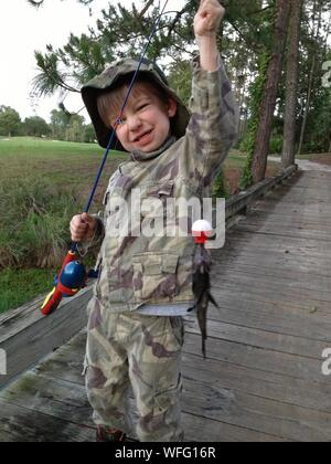 Portrait Of Boy In Camouflage Clothing Showing Fish In Fishing Rod While Standing Outdoors - Stock Photo
