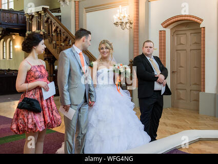 Young Couple Standing With Bridesmaid And Groomsman In Church - Stock Photo