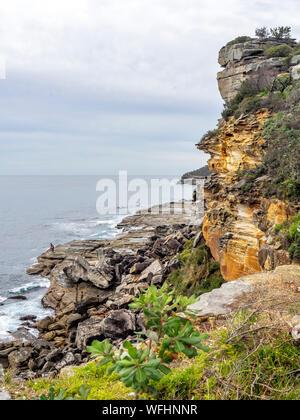 Two men rock fishing of rocks at Manly Headland Sydney NSW Australia. - Stock Photo