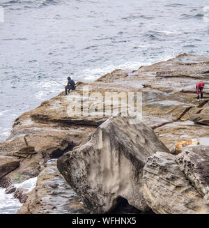 Two men rock fishing of rocks at Manly Headland Sydney NSW Australia. - Stock Photo