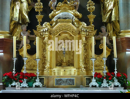 Mittenwald, Germany, August 10., 2019: Candle holder with candles, roses and jewellery in front of the gilded and silvered altar of a catholic church - Stock Photo