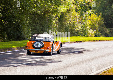 Morgan motor car driving along a country road in the English countryside - Stock Photo