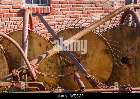 Closeup of an old, rusty tedder on a bricks wall. - Stock Photo