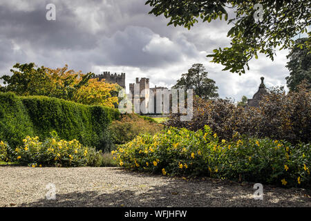 Raby Castle, Staindrop, Teesdale, County Durham, UK. 31st August 2019. UK Weather.  After a morning of sunny spells and showers the sun illuminates Raby Castle and its colourful gardens, which are starting to develop some autumnal colours.  Credit: David Forster/Alamy Live News - Stock Photo