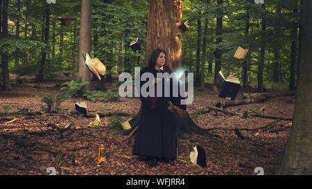 Teenage Girl Holding Magic Wand While Standing Amidst Books At Forest - Stock Photo
