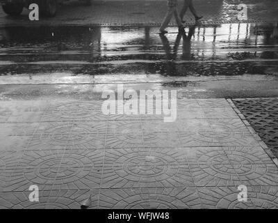 Low Section Of People Walking On Wet Street In Rainy Season - Stock Photo