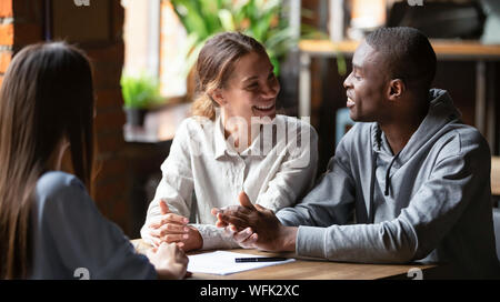 Smiling young mixed ethnicity couple talk decide on financial deal - Stock Photo