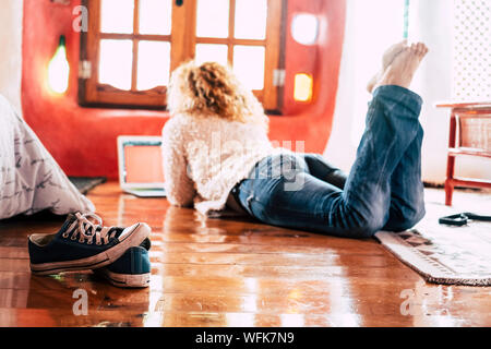 Hipster lady lay down on the floor at home working or doing modern shopping with laptop computer internet connected - concept of alternative independe