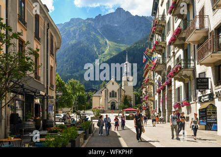 Street view with tourists, the church of Saint-Michel and Le Brévent mountain peak in the background in summer, Chamonix-Mont-Blanc, Alps, France