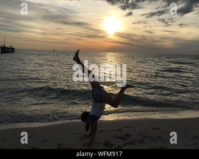 Young Woman Doing Handstand On Shore Against Sky During Sunset - Stock Photo