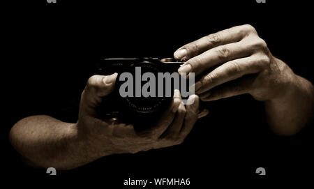 Cropped Image Of Hands Holding Camera Against Black Background - Stock Photo