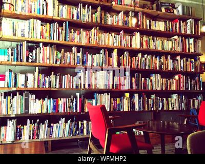 Empty Chair And Table Against Bookshelves In Library - Stock Photo