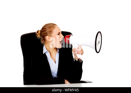 Businesswoman Shouting On Megaphone Against White Background - Stock Photo