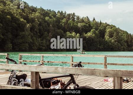 Bicycles Parked On Pier Over Lake By Forest - Stock Photo