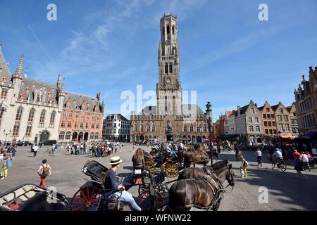 Belgium, West Flanders, Bruges, historical center listed as a UNESCO World Heritage, Grand Place, carriages in front of the Belfry over the Cloth Hall - Stock Photo