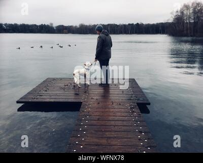 Full Length Of Woman Standing With Dog On Jetty Over Lake - Stock Photo