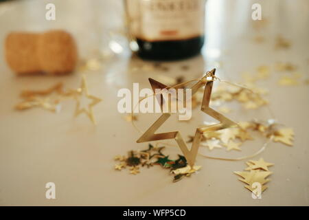 Close-up Of Star Shape Golden Christmas Decorations On Table - Stock Photo