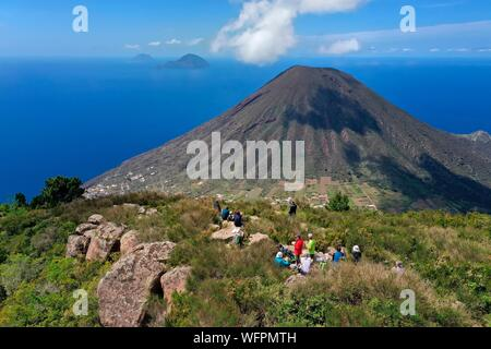 Italy, Sicily, Aeolian Islands, listed as World Heritage by UNESCO, Salina Island, hikers at the top of the old volcano Monte Fossa delle Felci observing the twin volcano Monte dei Porri during the picnic break, the islands of Filicudi and Alicudi in the background (aerial view) - Stock Photo