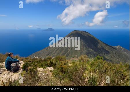 Italy, Sicily, Aeolian Islands, listed as World Heritage by UNESCO, Salina Island, hiker at the top of the old volcano Monte Fossa delle Felci observing the twin volcano Monte dei Porri, the islands of Filicudi and Alicudi in the background - Stock Photo