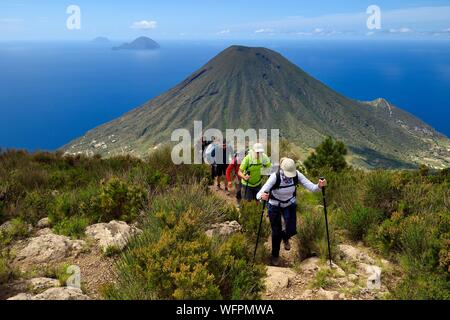 Italy, Sicily, Aeolian Islands, listed as World Heritage by UNESCO, Salina Island, hikers at the summit of the ancient volcano Monte Fossa delle Felci with the twin volcano Monte dei Porri, the islands of Filicudi and Alicudi in the background - Stock Photo